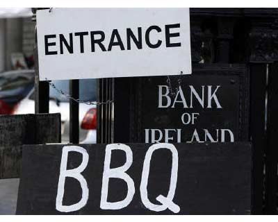 <p><b>Ireland set for majority stakes in leading banks. A placard advertising barbecued food rests against the entrance to the Bank of Ireland headquarters, Dublin</b>