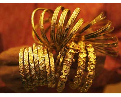 <p><b>A jewellery shop owner counts gold bangles before putting them in a locker, after displaying them to a customer at a jewellery shop in Kolkata</b>