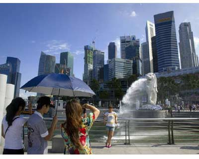 <p><b>A tourist poses for a photo in front of the Merlion, a mascot of Singapore, and the financial district skyline in Singapore</b>