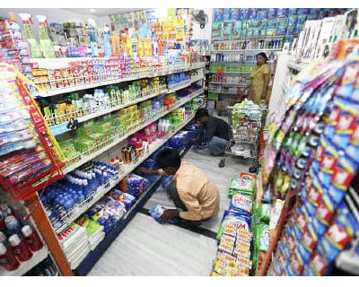 <p><b>Workers arrange consumable goods as a customer (back) shops at a grocery store in Lucknow</b>
