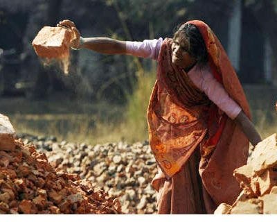 <p><b>A woman throws bricks to be used for construction purposes in Varanasi</b>