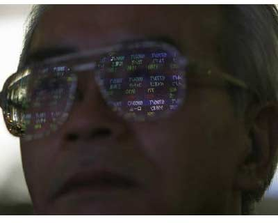 <p><b>A stock quotation board is reflected on a pedestrian's spectacles in Tokyo</b>