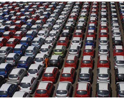 <p><b>An employee walks between parked Hyundai cars ready for shipment at a port in Chennai</b>