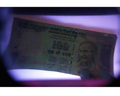 <p><B>A man uses an electronic machine to check a currency note at a money exchange shop in Siliguri</B> </p><p> The rupee moved in a tight range on Friday afternoon with mild losses in shares and the dollar overseas providing little direction ahead of the Federal Reserve chairman&#39;s speech on the US economy. </p><p> * Ben Bernanke is scheduled to speak at an annual meeting of the world&#39;s central bankers in the US state of Wyoming at 1400 GMT, with market players looking for any clues on his plan to boost measures to support the economy. </p><p> * At 2 pm, the partially convertible rupee was at 46.86/87 per dollar, marginally below 46.84/85 at close on Thursday. It has moved in range of 46.8150 to 46.89 so far. </p><p> * The dollar rose against the yen on Friday, trimming earlier losses due to wariness on possible measures from Japanese authorities to stem the yen&#39;s rise. </p><p> * The index of the dollar against six majors was marginally lower. Dealers expect the