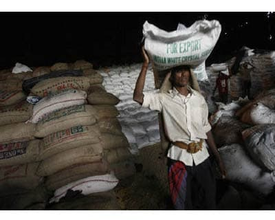 <p><b>A worker carries a sack of sugar at a food warehouse in Mumbai</b>