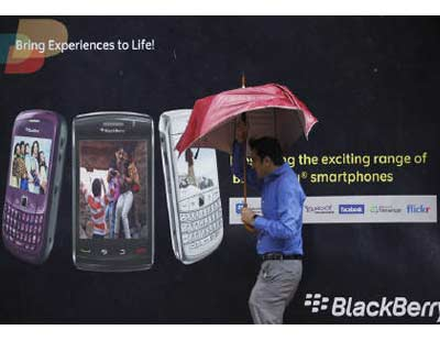 <p><b>A man tries to hold on to his umbrella as he walks past a Blackberry advertisement billboard in Mumbai</b> </p><p> Indian companies are mulling options that include leaving RIM for other smartphone makers as they face a threatened ban on BlackBerry services that could disrupt business. </p><p> RIM's rivals Apple Inc and Nokia would be among the biggest gainers if India blocks BlackBerry services. Both firms are waiting to gain share in a market that has been mostly dependent on BlackBerry. </p><p> BlackBerry, once a synonym for safe corporate communication faces an Aug 31 deadline for giving Indian security agencies access to its corporate email and messenger services, failing which the services would be blocked, the government has said. </p><p> GE, Infosys Technologies Ltd would look at using alternate services for communications to ensure that its business was not affected if some BlackBerry services were banned. </p>