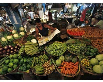 <p><b>A vegetable seller reads a newspaper as he waits for customers at a market in Kolkata</b>