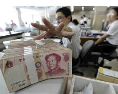 <p><b>An employee reaches for a bundle of 100 yuan banknotes at a branch of Bank of China in Hefei, Anhui province</b>