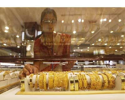 <p><b>A saleswoman arranges gold jewellery inside a showroom in Kolkata</b>