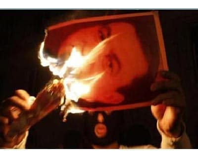 <p><b>A protestor burns a picture of Egypt president Hosni Mubarak after clashes in Cairo</b>