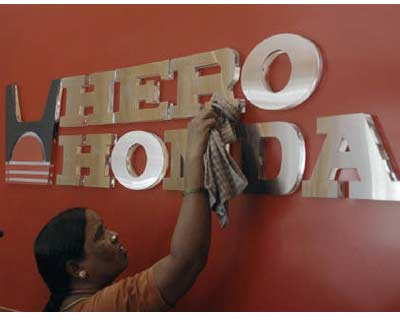 <p><b>A worker cleans a Hero Honda logo inside its showroom in Hyderabad</b>