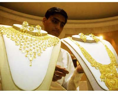 <p><b>A salesman arranges gold necklaces at a jewellery shop in Agartala</b>