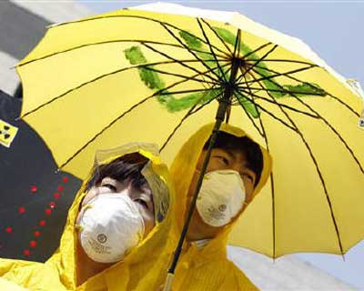 """<b><p>People wearing masks and raincoats take part in an anti-radioactivity rally to urge the government to quickly release information about """"radioactive rain"""" and risks of radioactivity, near the Integrated Government Complex in Seoul.</b> </p><p>Japan&#39;s government has downgraded its assessment of the economy for the first time in six months to reflect last month&#39;s devastating earthquake and tsunami, while wholesale prices rose at the fastest pace in more than two years in an ominous sign for company profit margins. </p><p>A loss of electricity from a crippled nuclear power plant and radiation leaks could weigh on the outlook for some time, the government warned on Wednesday, though it still expects the economy to recover later this year as reconstruction begins in the northeastern areas wrecked by the tsunami. </p><p>Higher input costs could also squeeze profit margins at companies struggling to secure enough parts to keep their factories running. </p>"""