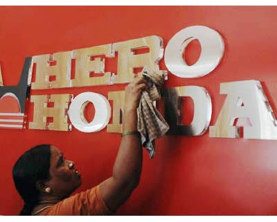 <p><b>A worker cleans the Hero Honda logo</b>