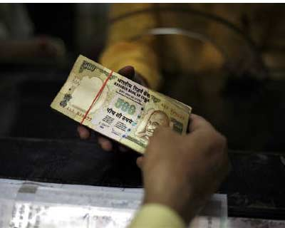 <b><p>A man deposits money in a bank in Amritsar.</b> </p><p> The rupee slid 2.4% on the day to 49.54 per dollar, its lowest level in more than 28 months, as global risk aversion prompted investors to move into safer assets like debt. </p><p> At 4:50 p.m. (1120 GMT), the partially convertible rupee was at 49.55/56 per dollar, its lowest since May 15, 2009. It had closed at 48.325/335 on Wednesday. </p>
