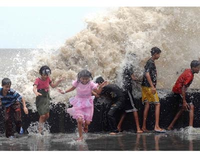 A huge wave lashes the shore, prompting some children to run for cover <P> <b>Picture by Divyakant Solanki</b> </P>