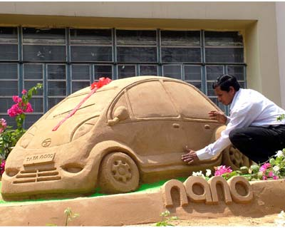 Sand artist Subal Maharana giving the final touches to his sculpture of the world&#39;s cheapest car, the Tata Nano, outside the State Bank of India office in Bhubaneswar
