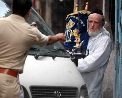 A man from the Zaka group holding the religious things of Israeli families who were shot dead during the terrorist attack in Mumbai. Zaka is a group dedicated to collecting and arranging the body parts and blood of Jews so that they can be returned to family members and afforded a dignified burial according to Jewish law.  <br><br> <i>Picture by Divyakant Solanki</i>