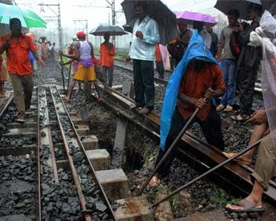 Workers fix a railway track in Thane