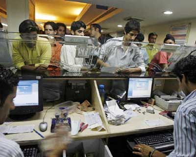 File photo of people transacting in a bank in Srinagar. Several banks have said they see stable lending rates and profits in the near term despite an unexpected repo rate hike by the Reserve Bank of India on intensifying inflationary pressures, thoug