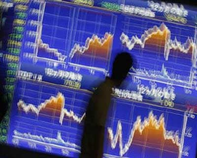</b><p>Passers-by walk past a board showing graphs of Japan&#39;s stock price indexes, outside a brokerage in Tokyo.</b>