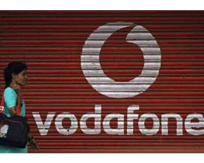 <p><b>A woman walks past a Vodafone logo displayed on a shop in Mumbai</b>