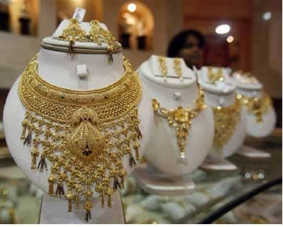 <p><b>A saleswoman stands behind the showcased gold necklaces at a jewellery showroom in Tripura</b>