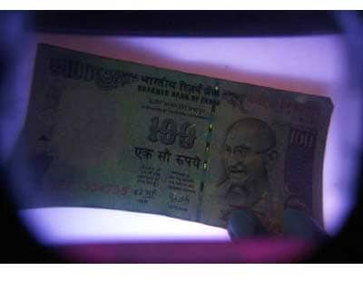 <p><b>A man uses an electronic machine to check a currency note at a money exchange shop in Siliguri</b>