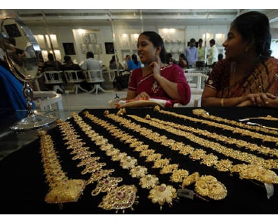<p><b>A customer looks in a mirror after wearing a gold earring inside a jewellery shop in the southern Indian city of Hyderabad</b>