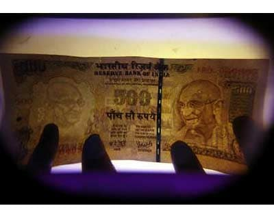 <p>A man uses an electronic machine to check a currency note at a money exchange shop in Siliguri</p><p><b>The rupee gained for the fourth session on Tuesday and hovered near a two-week high, helped by foreign fund inflows on the back of strong local