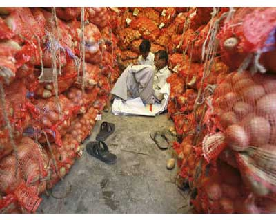 <b><p>Men sit amid stacked sacks of potatoes at a vegetable wholesale market in Noida, on the outskirts of New Delhi.</b>