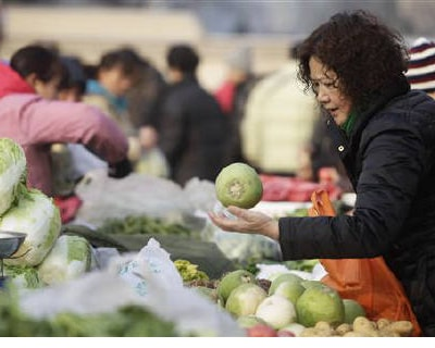 <p><b>A woman selects a turnip at a morning market in central Beijing</b> 