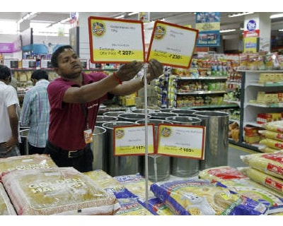 <p><b>A worker of a food superstore arranges price tags of the products inside a mall in Ahmedabad</b>  </p><p> India's food price index rose 9.42% and the fuel price index climbed 12.79% in the year to March 5, government data on Thursday show