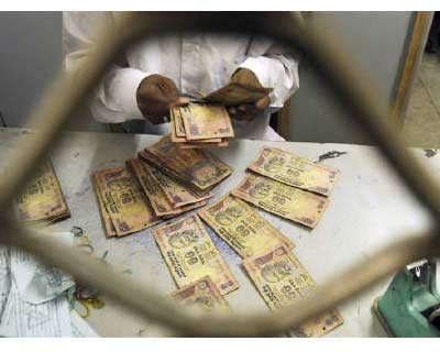 <p>An employee sorts Indian currency notes at a cash counter inside a bank in Agartala</p><p><b>The rupee pulled back from the two-year low touched earlier on Tuesday comforted by gains in domestic equities and a rebound in the euro.</b></p><p>* Trad