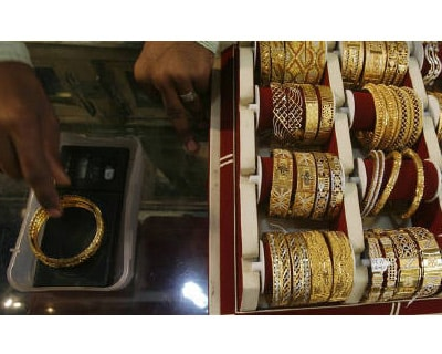 <p><b>A shopkeeper weighs gold bangles at a jewellery shop in Mumbai</b>