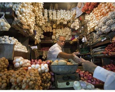 <p><b>A vendor exchanges money with a customer at a shop selling garlic, onions and potatoes at a wholesale market in Mumbai</b></p><p>India&#39;s food price index rose 7.58% and the fuel price index climbed 11.89% in the year to July 9, government d