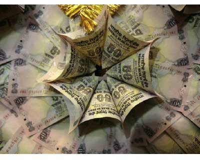 <p>Currency notes are stapled to form a garland at a market in Jammu</p><p><b>The rupee touched the 52 per dollar mark for the first time in 32-1/2 months on Monday as domestic equities weakened and oil importers bought dollars.</b></p><p>At 3:13 pm,