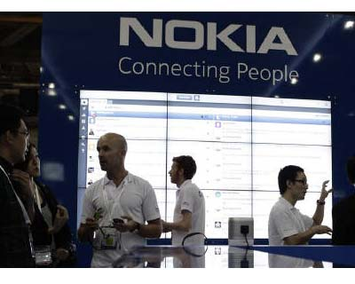 <p><b>Staff members speak to trade visitors at the Nokia booth at the CommunicAsia expo in Singapore</b></p>Finnish cellphone maker Nokia said on Wednesday it would merge its independent Navteq mapping unit with its services business to tap into surg