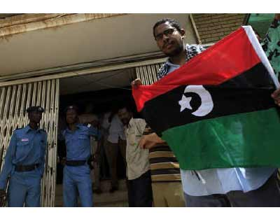 <p>Police stand guard as a Libyan resident holds the Kingdom of Libya flag while storming the Libyan embassy to look for work opportunities in Khartoum</p><p><B>Investors peering through the receding fog of war will find plenty of promise and a few p