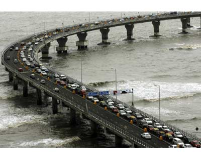 <p><b>Traffic moves along the Bandra-Worli sea link in Mumbai</b></p><p>Hindustan Construction Co on Thursday reported a 90% plunge in June-quarter net profit, hurt by higher interest rates and a slowdown in the infrastructure sector, sending its sha