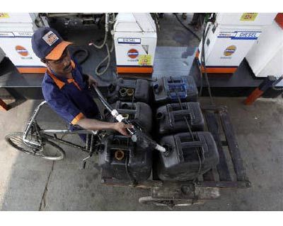 <p><b>A worker fills jerrycans with diesel at a fuel station in Kolkata</b>