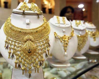 <p><b>A saleswoman stands behind the showcased gold necklaces at a jewellery showroom in Agartala</b>