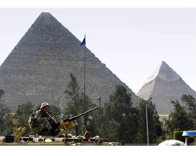 <p><b>Army soldiers atop an Armoured Personel Carrier (APC) guard the area near the Pyramids in Cairo</b>