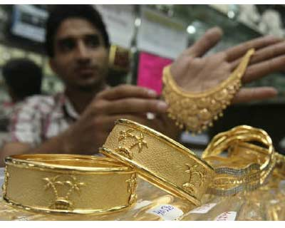 <P> A salesman displays gold ornaments at a jewellery showroom in Chandigarh.  </P><P> India&#39;s gold buying retreated on August 4 afternoon after picking up from last week as prices revisited the keenly-watched Rs 18,000 mark, with traders eyei