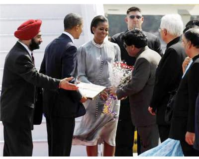 <p><b>US first lady Michelle Obama receives flowers as she stands next to US President Barack Obama (2nd L) after arriving on Air Force One in Mumbai November 6, 2010. </b>