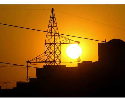 <p><b>Sun sets behind a power tower near a building in New Delhi</b>