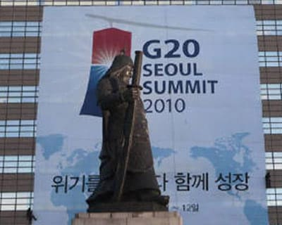 <P><b>Workers add the finishing touches to a G20 poster in Seoul, behind a statue of Admiral Yi Sun-sin</b>