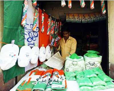 <p>A man arranges green powder, flags, umbrellas and caps bearing the symbol of the Trinamool Congress party in Kalighat district, the neighbourhood where its leader Mamata Banerjee lives, in Kolkata</p><p><b>A shift of power called for a mass celebr