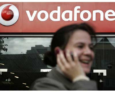 <p>A woman talks on a mobile telephone as she passes a Vodafone store in central London</p><p><b>Vodafone, the world&#39;s largest mobile operator by revenue, surprised investors with an upbeat outlook for 2012 on Tuesday after posting resilient resu