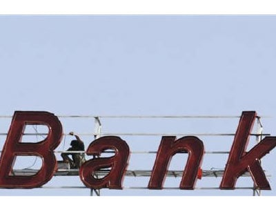 <p><b>A labourer works on the sign of a bank building in Ahmedabad</b></p><p>The government on Tuesday sought parliamentary approval to amend a banking law for allowing investors in private banks to have voting rights proportional to their shareholdi